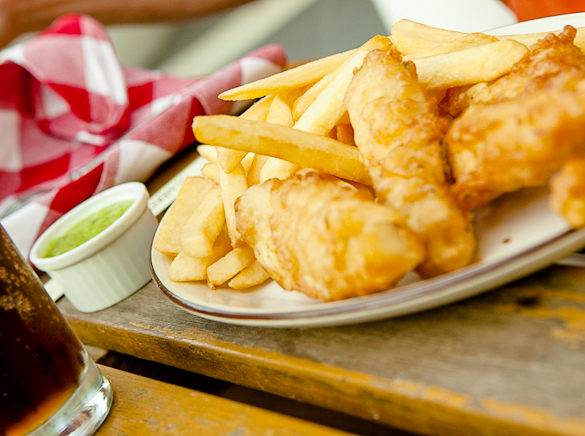A picture of fish & chips served with mushy peas in London