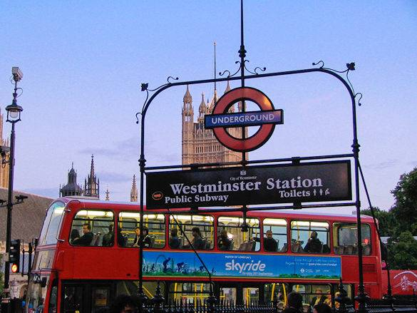 Typical London scene of an Underground station, red double-decker bus and Westminster Palace
