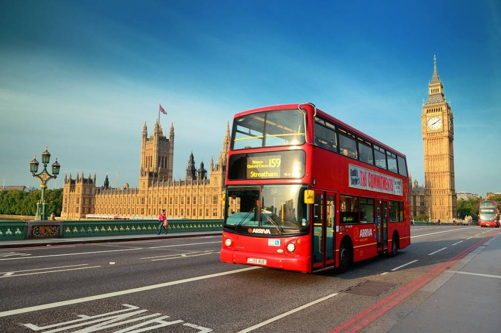 Image of a double decker bus on a road in front of the Palace of Westminster, London