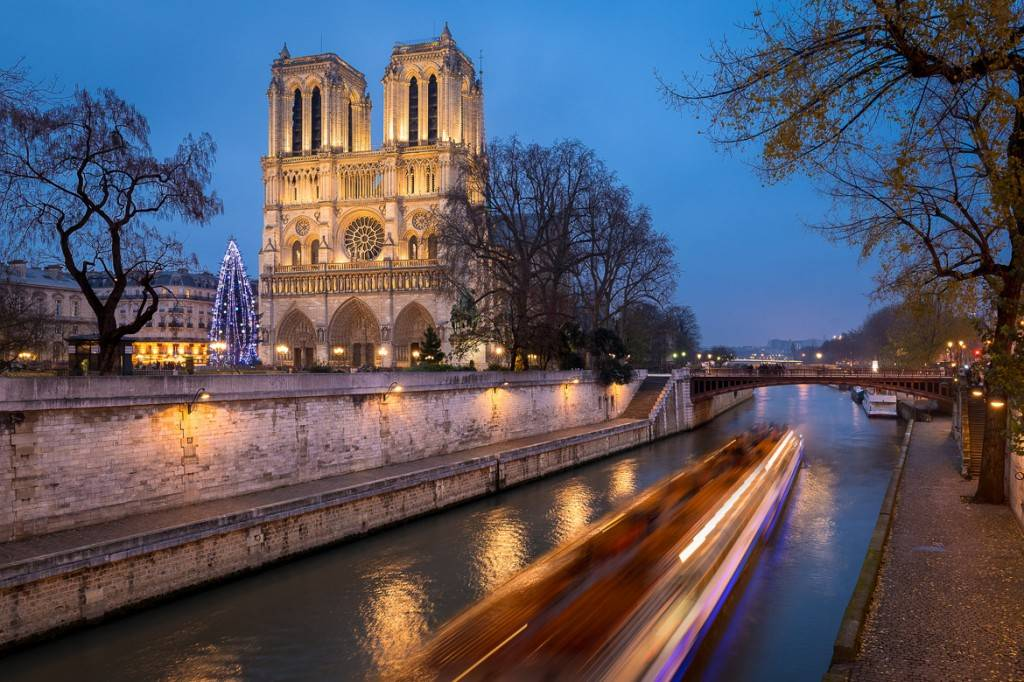 Image of the Seine River and a Christmas tree in front of Notre Dame Cathedral