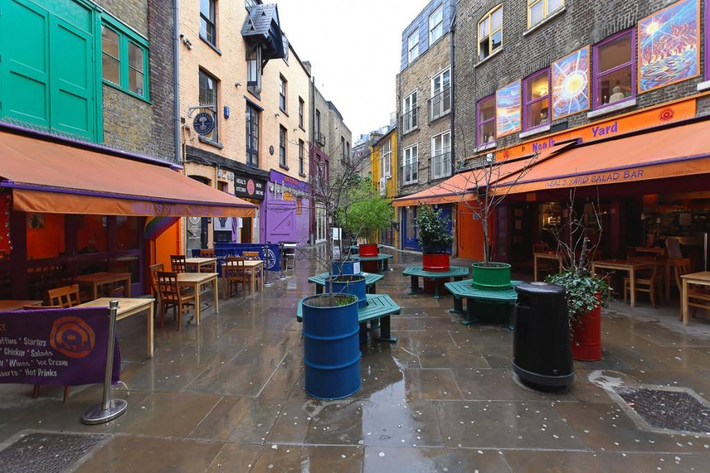 Image of the small sitting area in Neal's Yard, surrounded by the colorful buildings