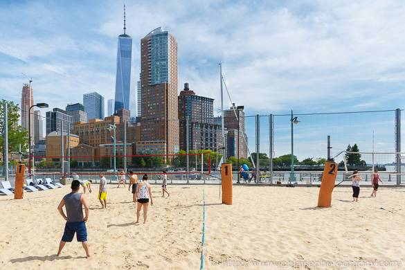 Picture of people playing volleyball with NYC skyline and Freedom Tower in background