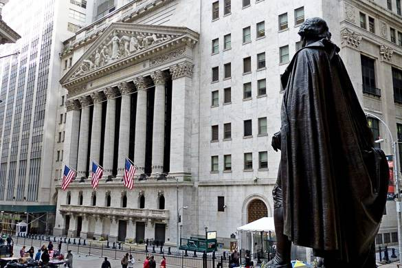 Image of the NYSE on Wall Street with American flag and statue if foreground