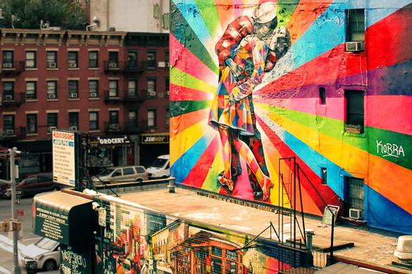 Image of street art graffiti on side of a building with iconic scene of sailor kissing woman in Times Square