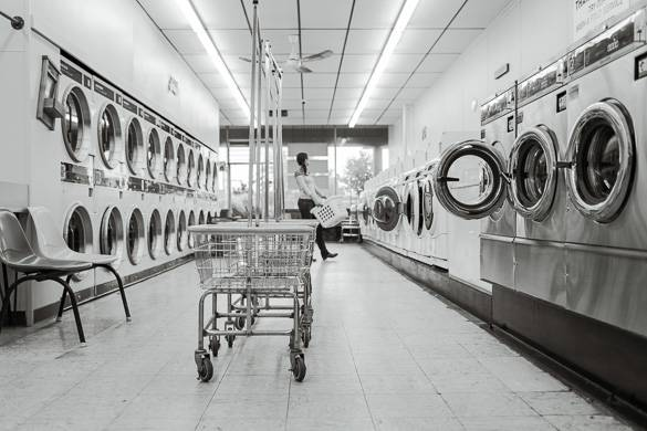Image of person standing in laundromat with rows of washers, dryers and laundry carts