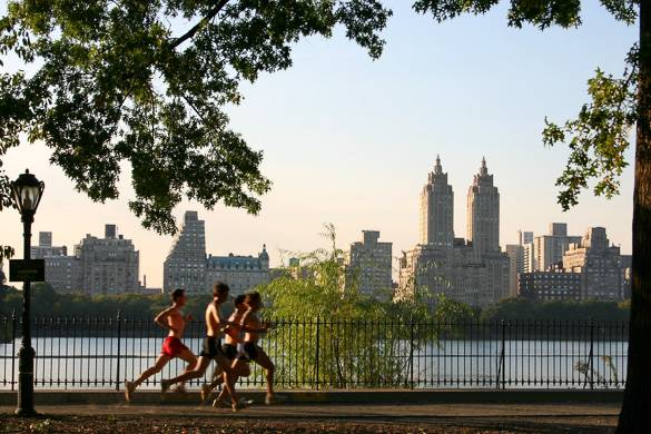 Image of joggers running alongside the Central Park reservoir at sunset