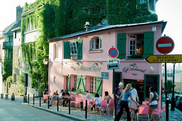 Image of La Maison Rose in Springtime, a pink colored restaurant on a corner in Montmartre