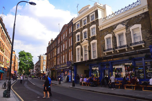 Image of a London street with pubs and cafes