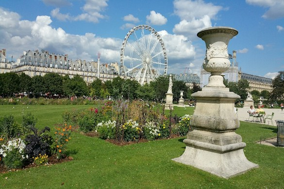 Image of park with plants and statues and Ferris wheel in the background