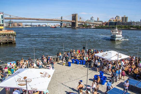 Image of people at an outdoor festival by the waterfront with Brooklyn Bridge and ferry in the background
