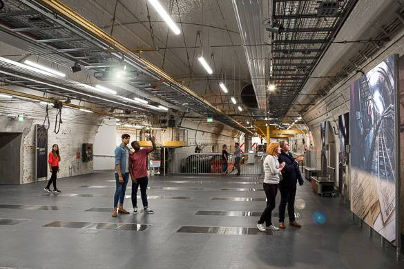 Image of people admiring artwork in the engineering depot at the Postal Museum