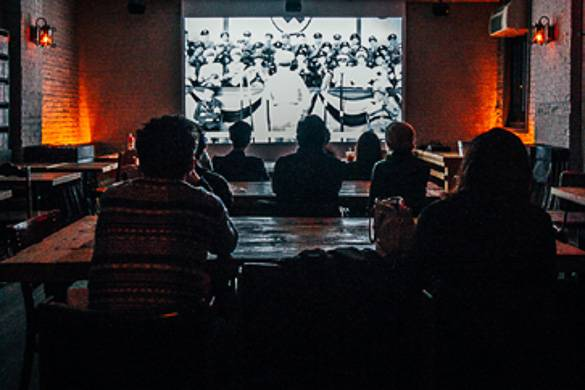 Image of people sitting at tables watching a film at Videology Bar