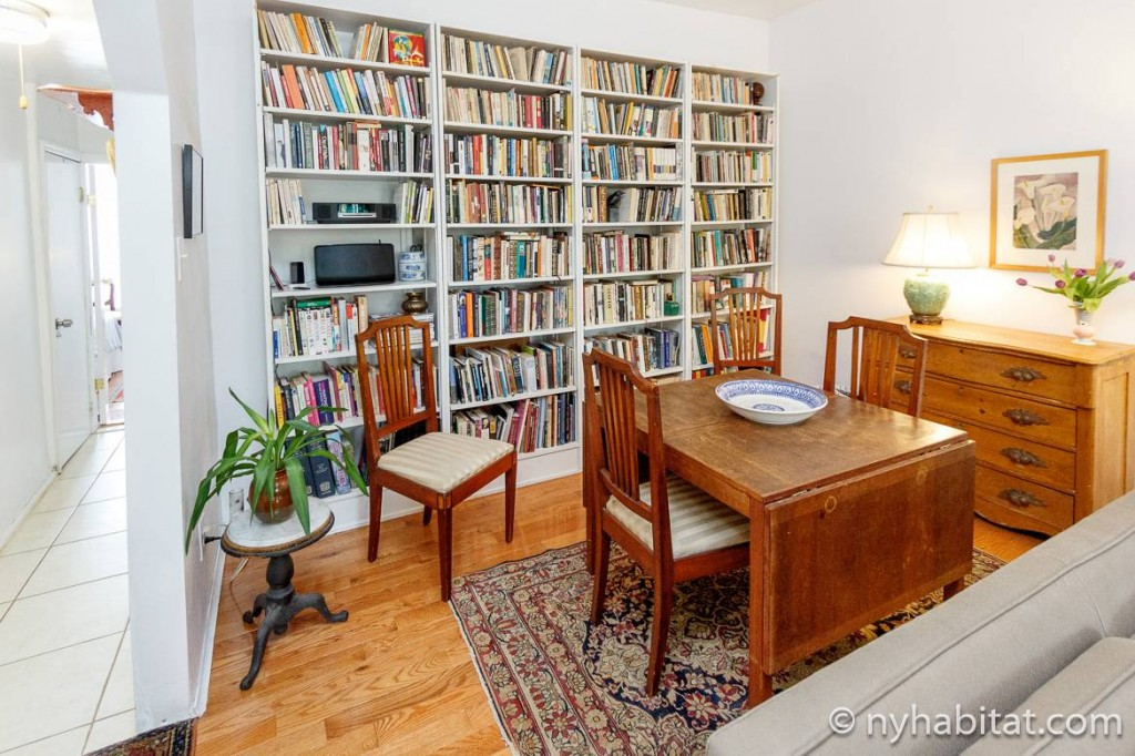 Image of dining table with built-in bookshelves lined with booked behind it