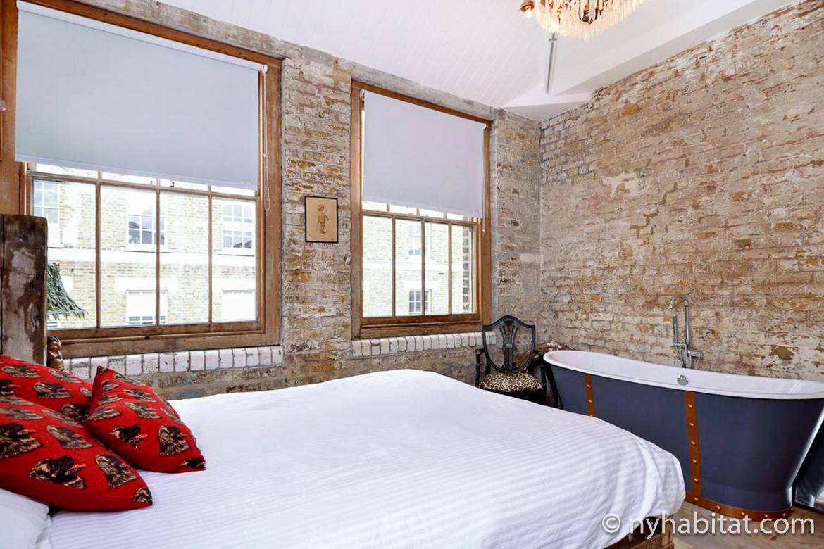 Image of bedroom of LN-573 with exposed brick walls and an antique tub