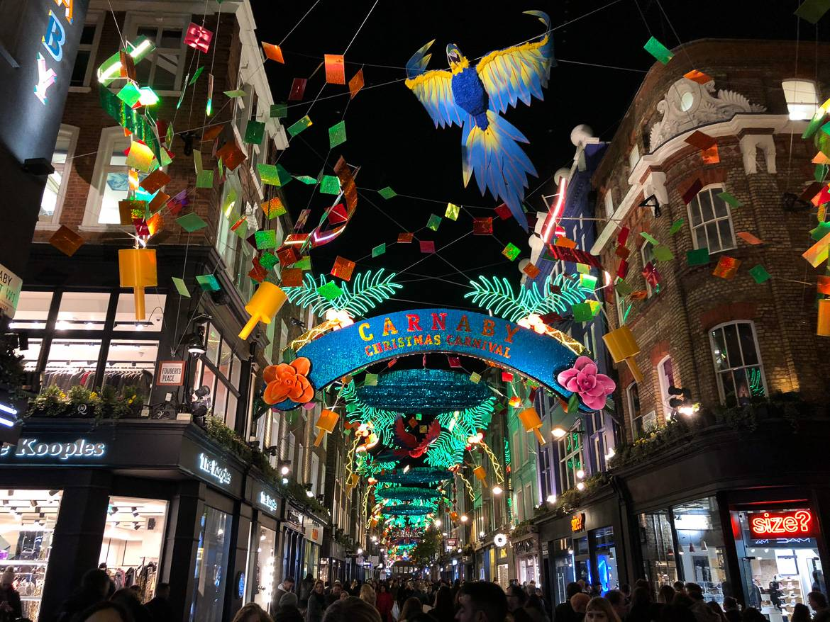 Image of Carnaby Street with colorful Christmas lights, people strolling the cobblestoned streets