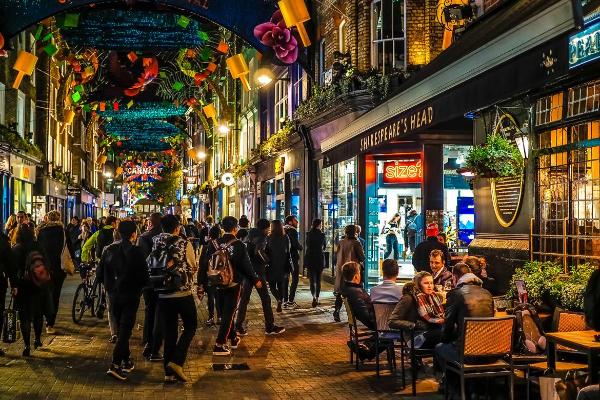 Image of nighttime lights over pedestrians shopping and sign saying Carnaby Street Carnival in SoHo, London