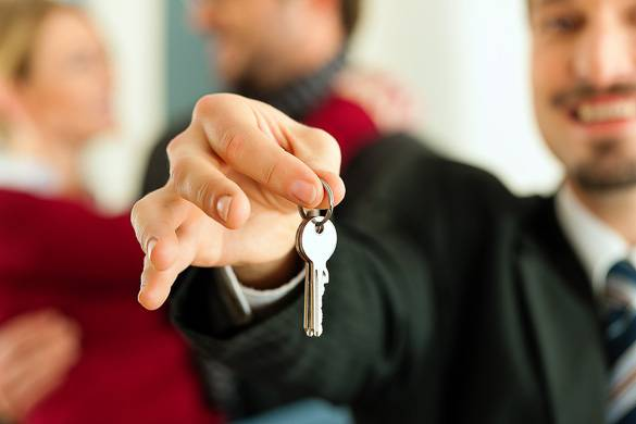 Foto eines Immobilienmaklers, der die Schlüssel für eine Wohnung überreicht