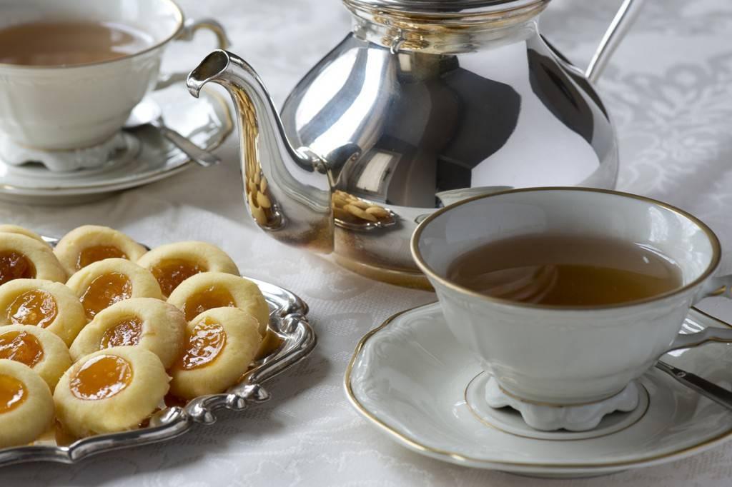 Bild eines traditionellen englischen Nachmittagstees mit Keksen, Teetasse, Untertasse und Kanne