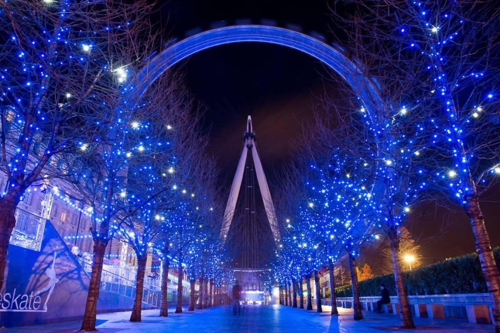 Bild des London Eye vor Bäumen geschmückt mit blauer Weihnachtsbeleuchtung