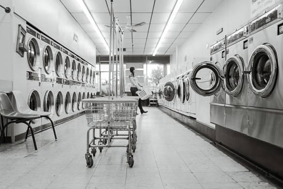 Bild einer Person, die in einem Waschsalon steht mit aneinandergereihten Waschmaschinen, Trocknern und Wäschewagen.