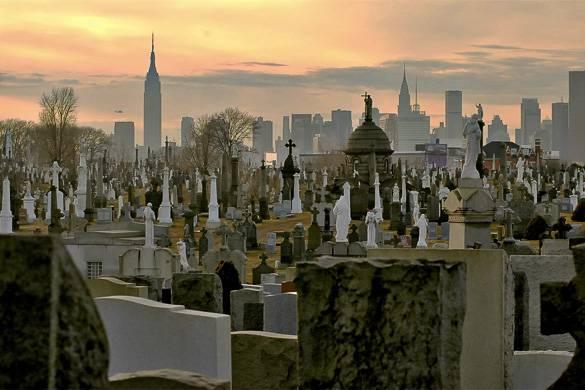 Bild von Gräbern mit der Skyline Manhattans im Hintergrund.