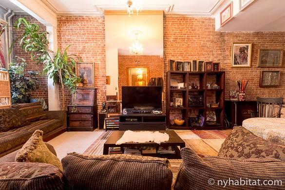 Bild des Wohnzimmers in NY-15886 mit freiliegenden Backsteinwänden und Kronleuchter über den Sofas.