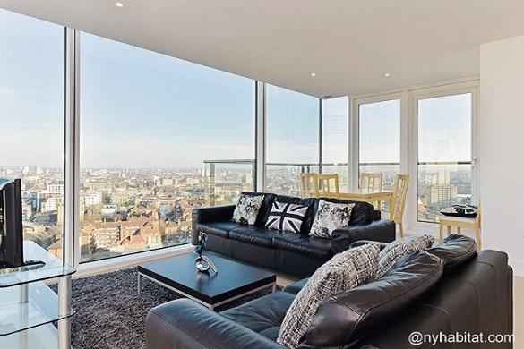 Bild mit schwarzen Ledersofas und Aussicht auf die Londoner Skyline durch eine Fensterwand