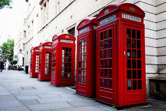 Bild mehrerer roter Telefonzellen, die eine Straße säumen