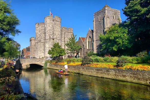 Bild eines Bootes auf dem Fluss in Canterbury mit historischem Gebäude im Hintergrund