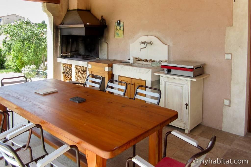 Photo du coin repas de la cuisine extérieure avec poêle à bois et évier