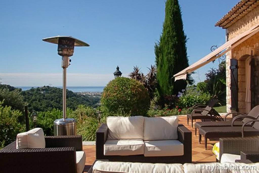 Photo d'une terrasse avec salon de jardin et chaises longues surplombant la mer Méditerranée