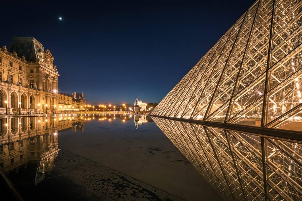 Photo d'une pyramide à côté d'un bassin miroir devant le musée du Louvre