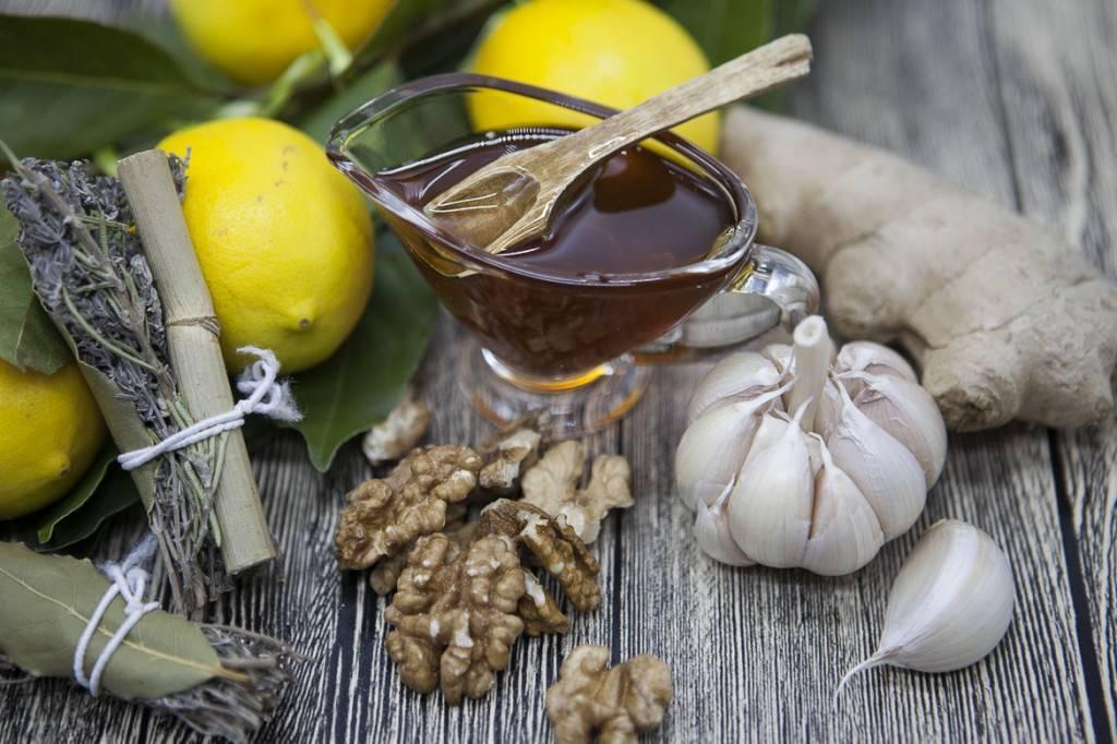 Photo illustrant des herbes de Provence, des citrons, du miel et de l'ail sur une table rustique en bois