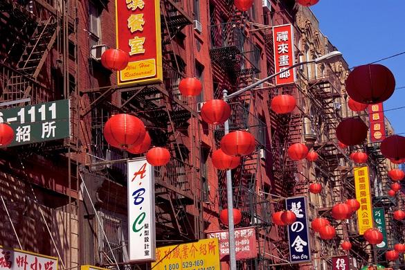 Photo de panneaux écrits en chinois et de lanternes chinoises dans Chinatown à New York.