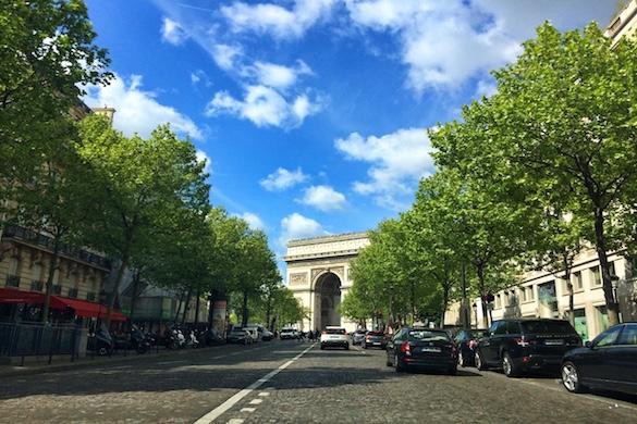 Photo de l'Arc de Triomphe au fond d'une rue arborée.
