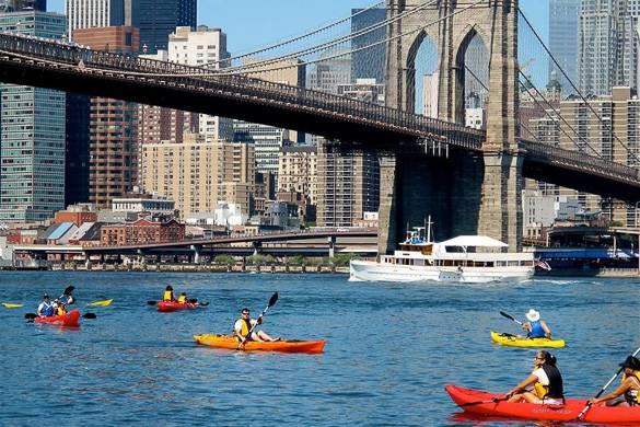 Photo de personnes faisant du kayak sous le pont de Brooklyn avec la vue de la ville à l'horizon.