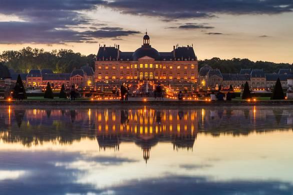 Photo d'un grand château au bord d'un lac au coucher du soleil