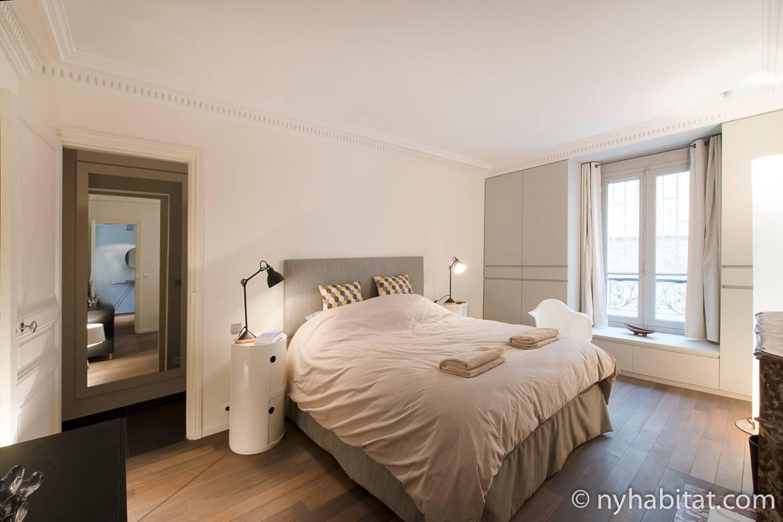 Photo de la chambre à coucher de l'appartement PA-4708 avec lit et coin lecture prêt de la fenêtre