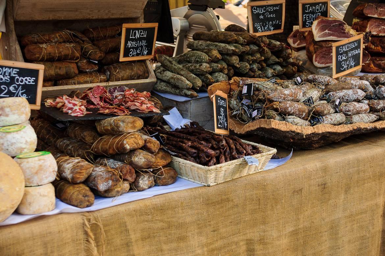 Immagine di un tavolo pieno di salsicce, formaggi e specialità francesi.
