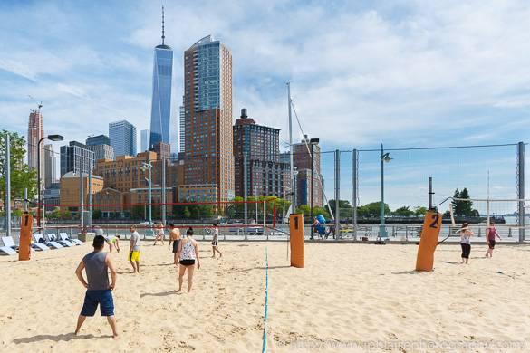 Foto di persone che giocano a beachvolley con lo skyline newyorkese e la Freedom Tower sullo sfondo