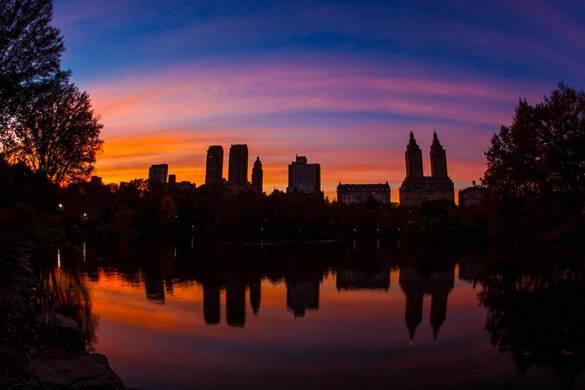 Immagine del profilo dell'orizzonte newyorkese al tramonto lungo il lago a Central Park.