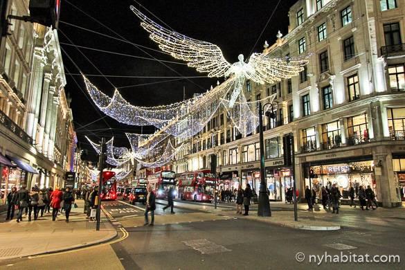 Immagine di una strada con molti negozi con luci festive colorate, autobus a due piani e addobbi luminosi a forma di angeli