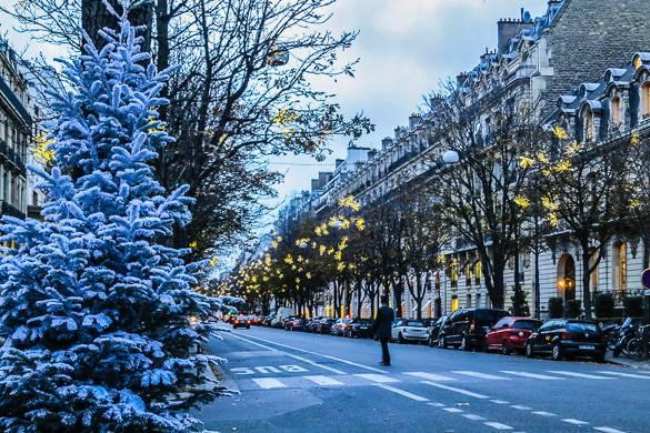 Foto di una strada di Parigi con luci natalizie gialle e un albero bianco