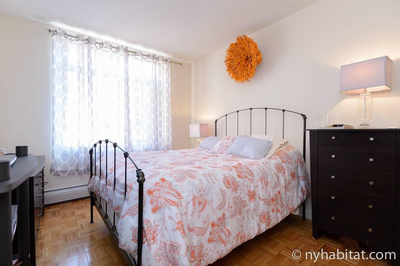 Immagine di una camera da letto in affitto dell'appartamento NY-16163 con un letto matrimoniale queen, una grande finestra e un armadio