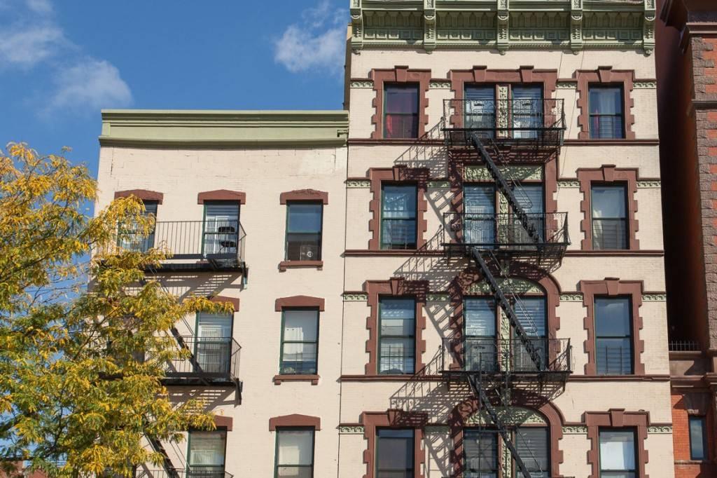 imagen de dos edificios contiguos uno a la izquierda con una silla en su salida