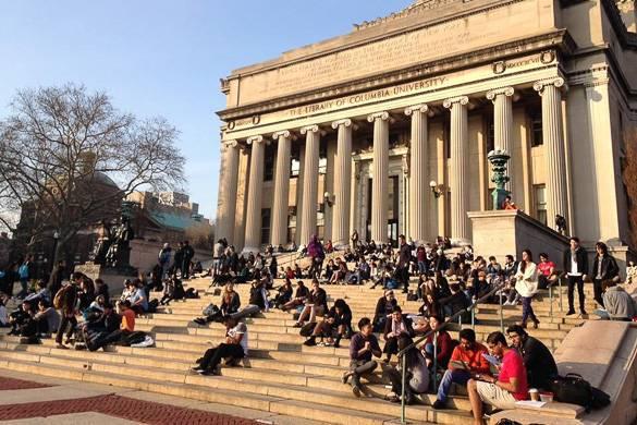 Imagen de la biblioteca de la Universidad de Columbia con estudiantes sentados en las escaleras.