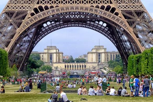 Fotografía de turistas disfrutando de un pícnic debajo de la Torre Eiffel