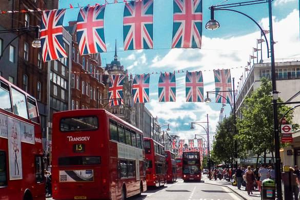 Fotografía de banderas británicas y autobuses de dos pisos