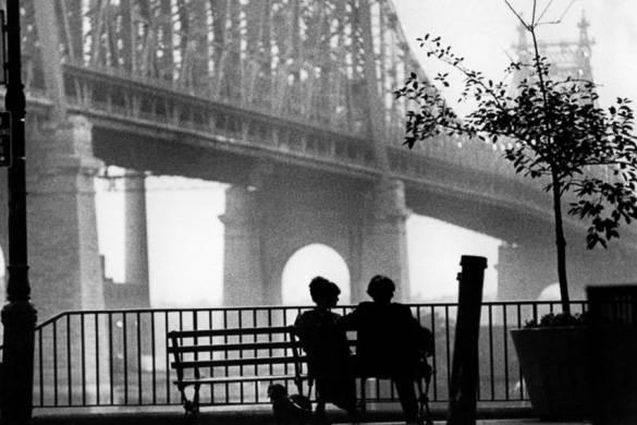 Imagen de personas sentadas en un banco con el Queensboro Bridge de fondo