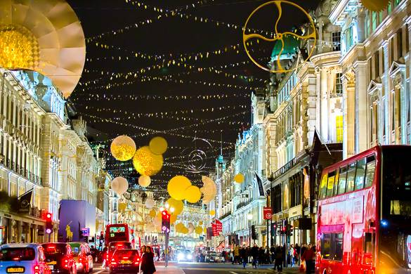 Imagen de una calle comercial con coloridas luces de Navidad, autobuses de dos pisos y gente de compras
